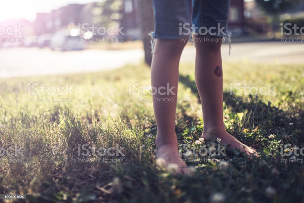 Little girl playing in the front yard stock photo
