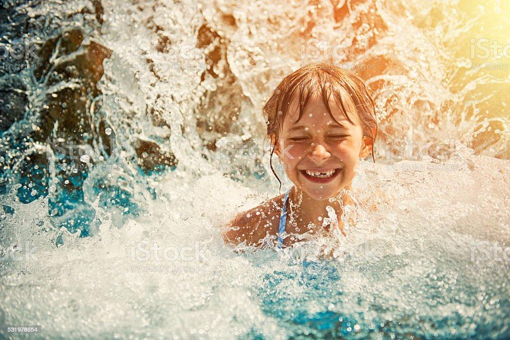 Mała dziewczynka gra w Wodospad w park wodny basen – zdjęcie