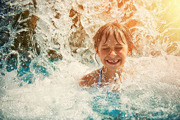 Little girl playing in waterfall in waterpark swimming pool stock photo