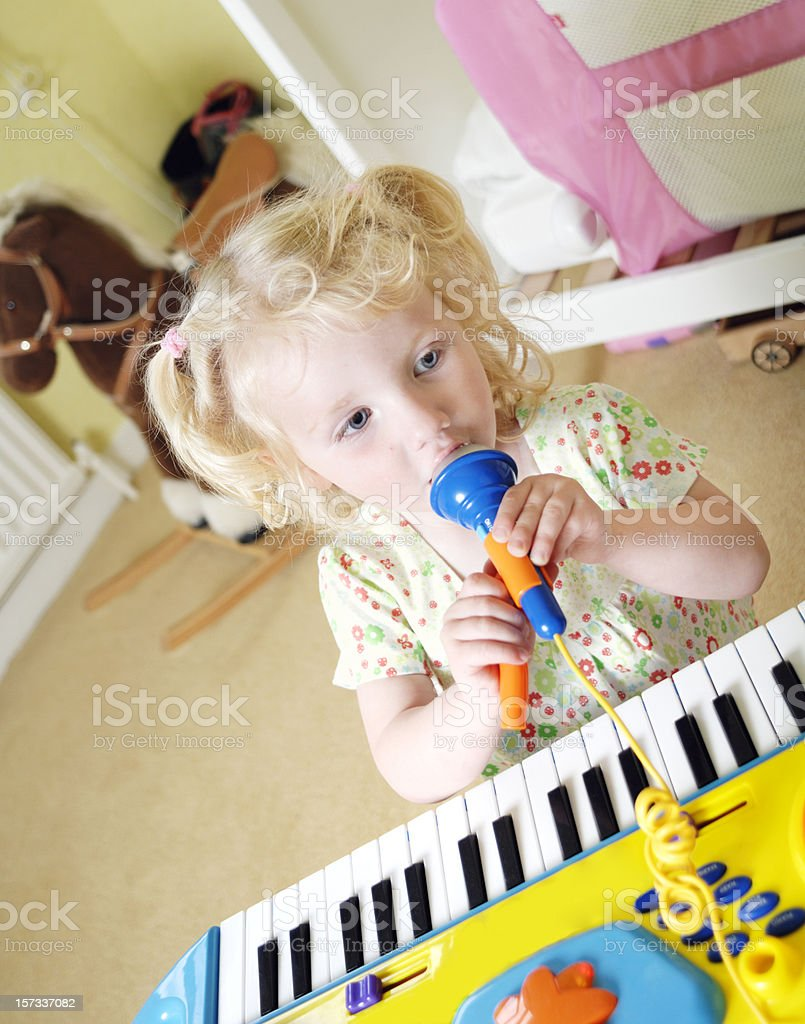 little girl playing keyboard and singing stock photo
