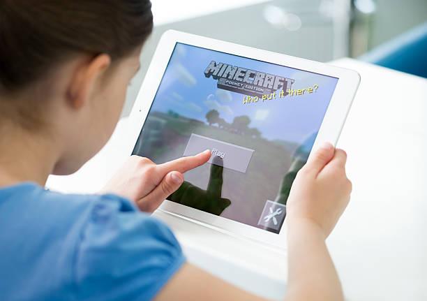 Little girl playing Minecraft on Apple iPad Air stock photo