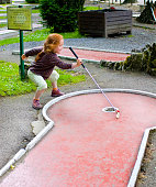 Little girl playing mini golf, her way