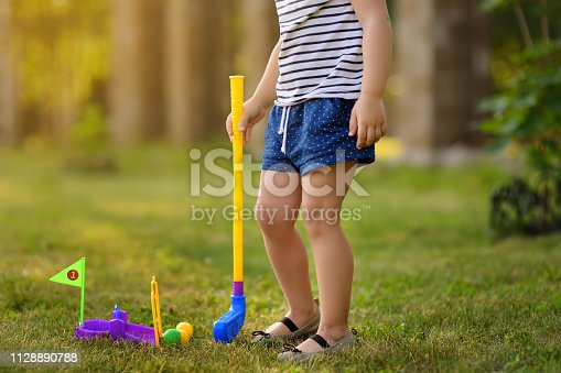 Little girl playing mini golf in spring park. Child having fun with active leisure on vacations. Baby on golf course.