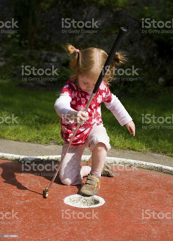 Little girl playing mini-golf one-handed, sitting down royalty-free stock photo