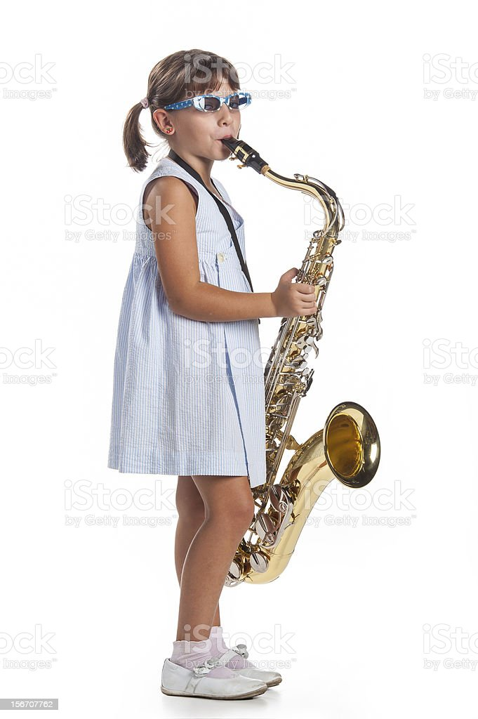 little girl playing music on saxophone royalty-free stock photo