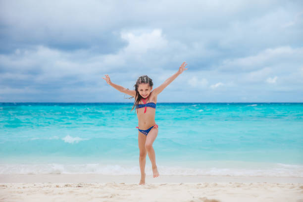little girl playing on a sandy beach - girl alone in swimsuit stock photos and pictures