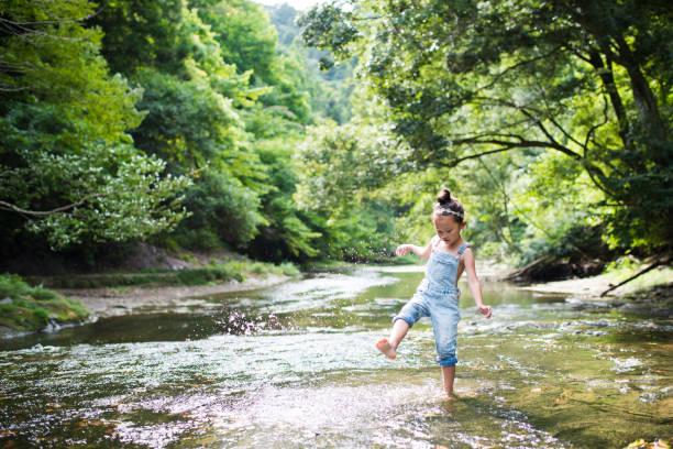 kleine mädchen spielen auf einen stream - bach stock-fotos und bilder