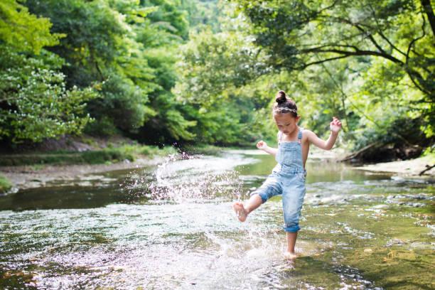 kleine mädchen spielen auf einen stream - kinder picknick spiele stock-fotos und bilder
