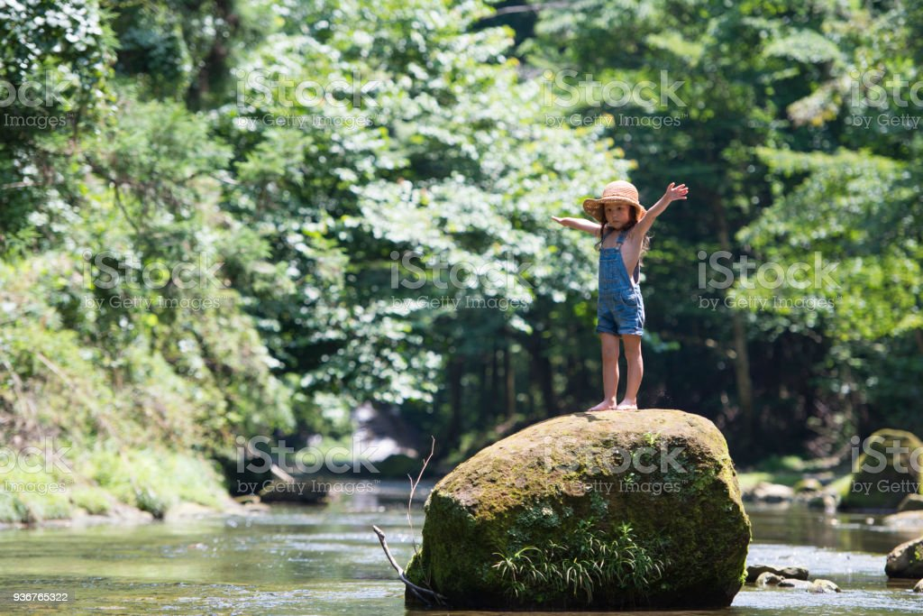 Little girl playing on a stream stock photo