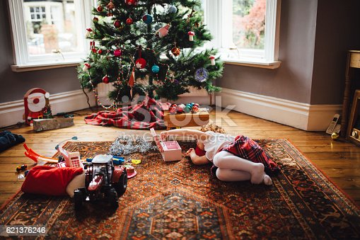 Christmas morning and a little girl is lying on the floor in front of the Christmas tree. The little redheaded girl is lying on her side playing with her new toys . A Christmas tree can be seen in the background and toys scattered around the floor.