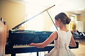 istock Little girl playing on grand piano 477938462