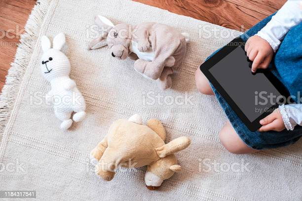 Little girl playing on her digital tablet on the floor picture id1184317541?b=1&k=6&m=1184317541&s=612x612&h=2uidvflw4j5dgztgq1g8ywj9tgjwciwnhlshs zcxno=