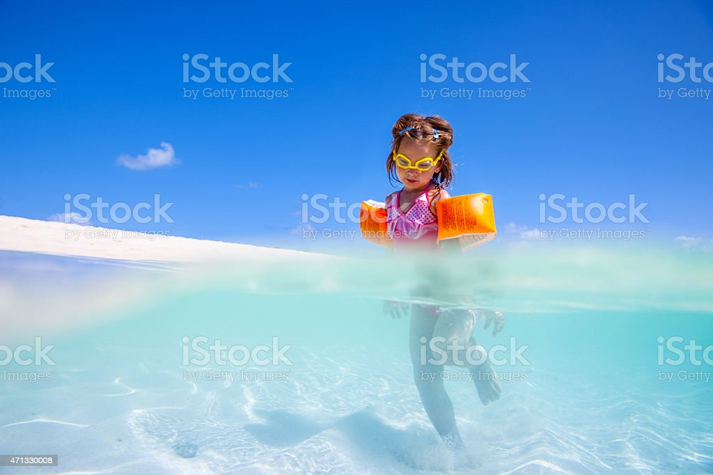 Little girl playing on idylic beach stock photo