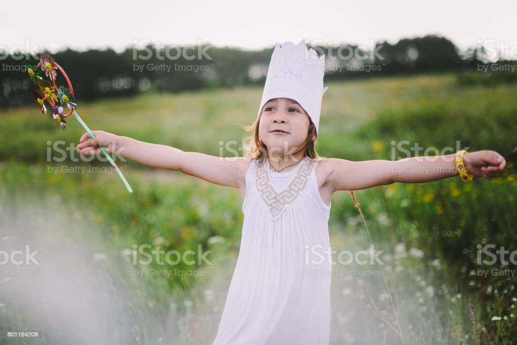 Little girl playing on meadow stock photo