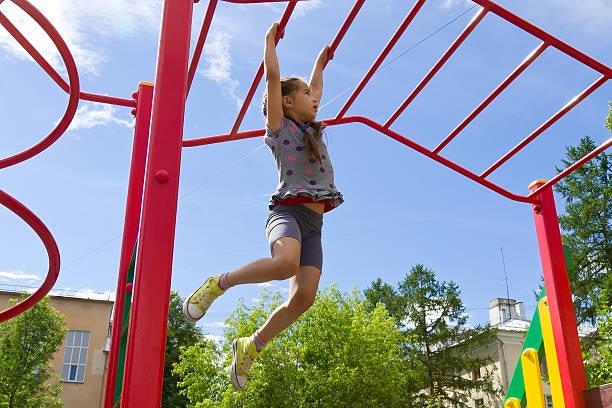 little girl playing on playground, hanging walk along monkey bars - schommelen bungelen stockfoto's en -beelden