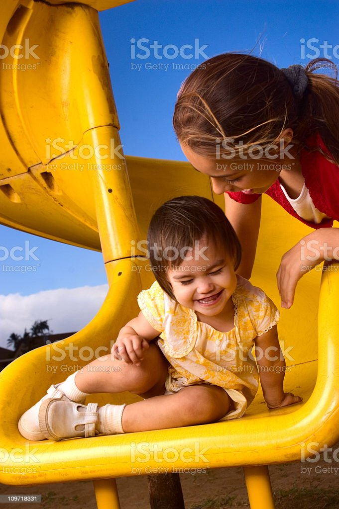 Little Girl Playing on Playground Slide with Mother royalty-free stock photo