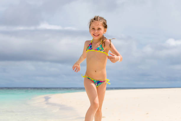 Little Girl Playing On Sandy Beach stock photo