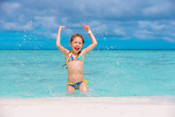 little girl playing on sandy beach - girl alone in swimsuit stock photos and pictures