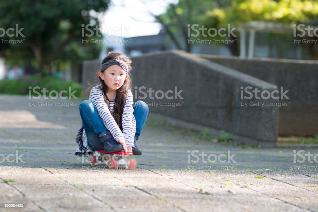 Little girl playing on skateboard stock photo