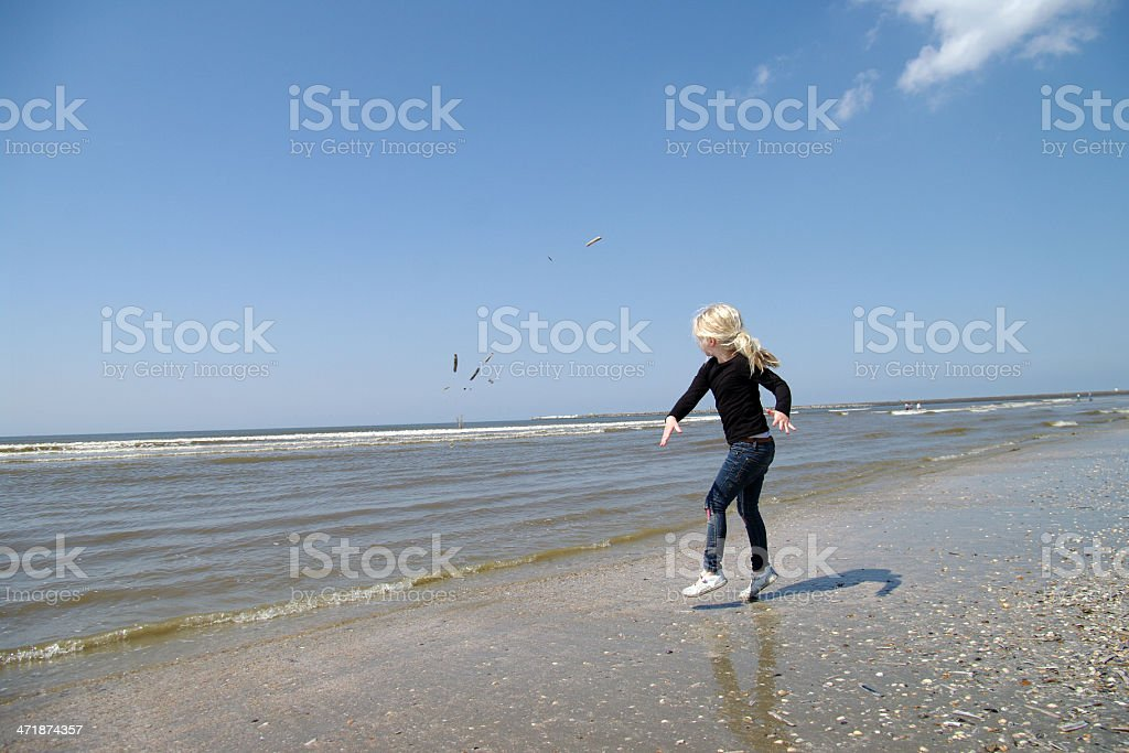 Little girl playing on the beach royalty-free stock photo