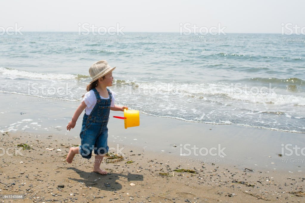 Little girl playing on the beach stock photo