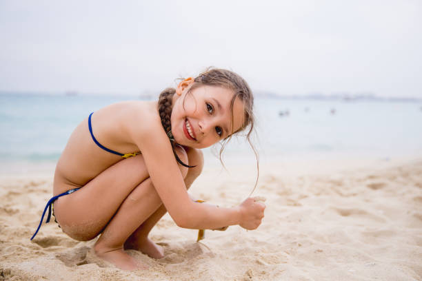 little girl playing on the dubai beach - girl alone in swimsuit stock photos and pictures