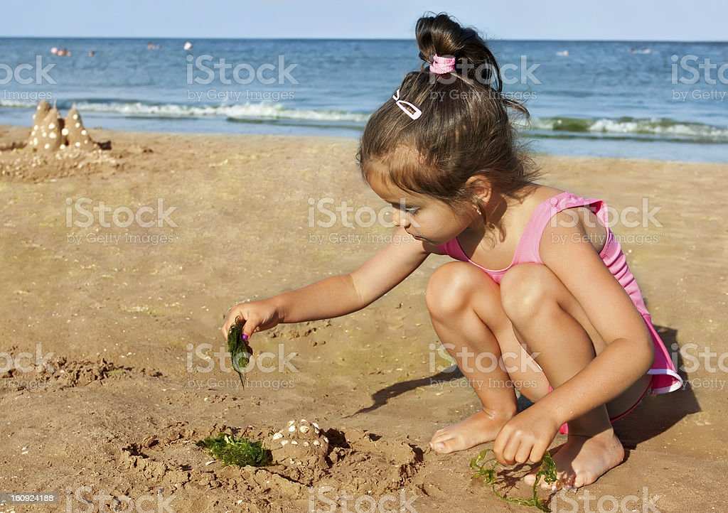 Little girl playing on the seaside royalty-free stock photo