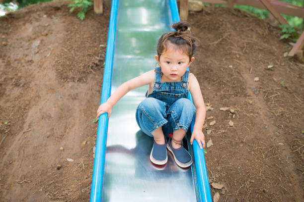 Little girl playing on the slide stock photo