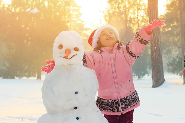 little girl playing outdoors with a snowman - schneemann bauen stock-fotos und bilder