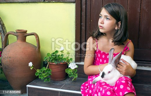 A little girl playing outside with a bunny in hands.She is having a great time.