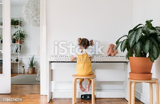 istock Little Girl Playing Piano 1194274274