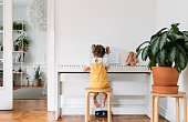 Back view of cute little girl with pigtails playing a piano.