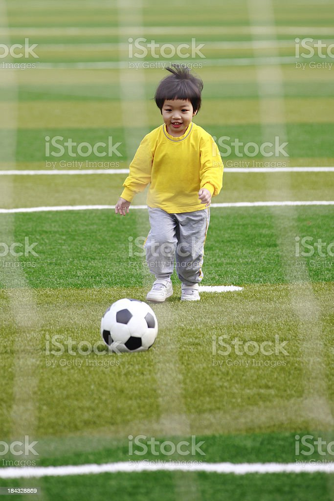 Little Girl Playing Soccer On Lawn royalty-free stock photo