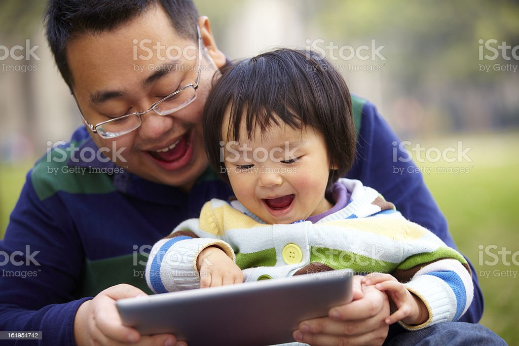 little girl playing tablet with her father outdoor royalty-free stock photo