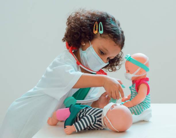 une petite fille jouant le docteur - masque enfant photos et images de collection