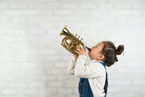 Little girl is playing a small trumpet