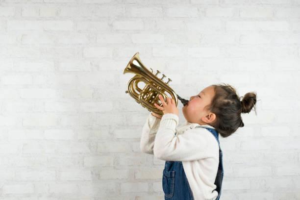 어린 소녀는 트럼펫 연주 - 트럼펫 뉴스 사진 이미지