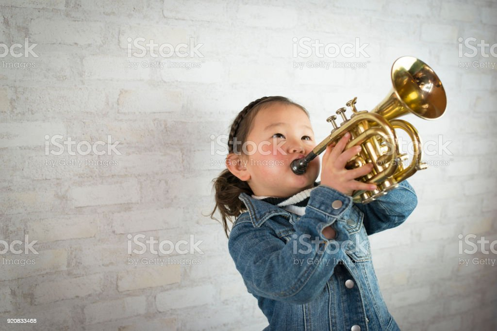 Little girl playing the trumpet stock photo