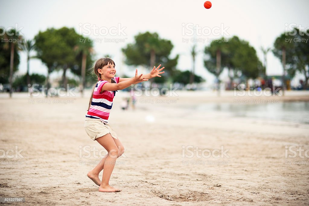 Little girl playing throw and catch on the beach stock photo