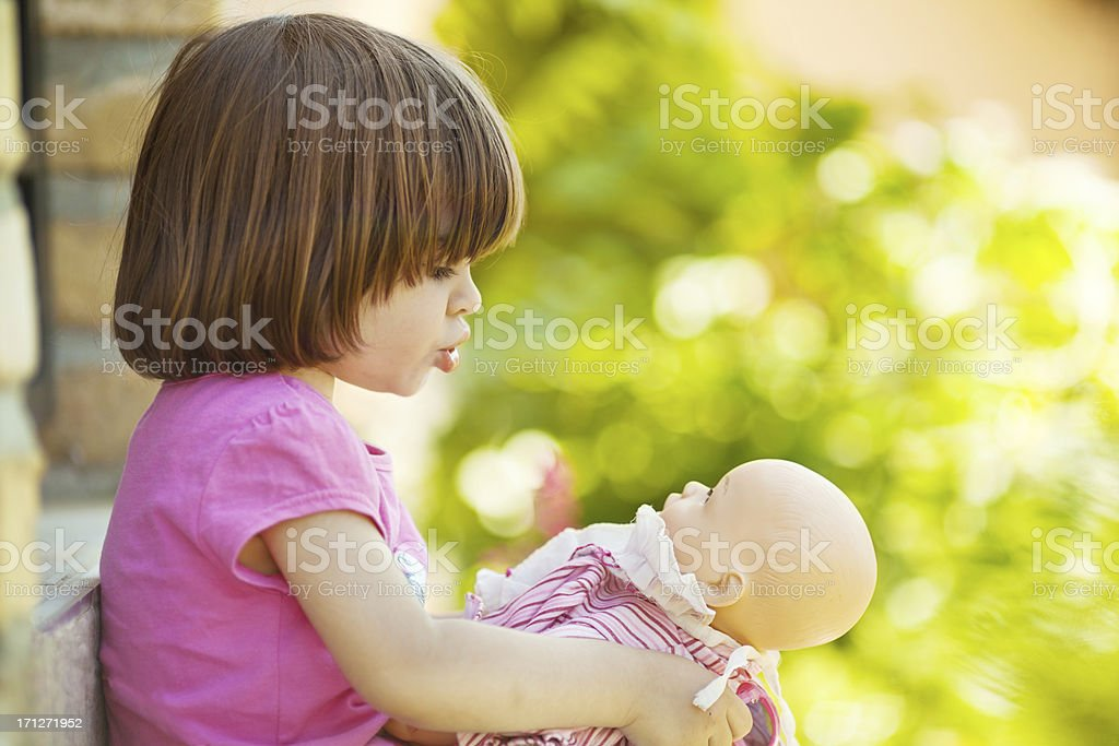 Little girl playing to be mommy stock photo
