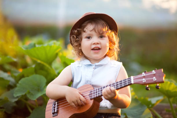 kleine mädchen spielt ukulele natur - ukulele songs stock-fotos und bilder