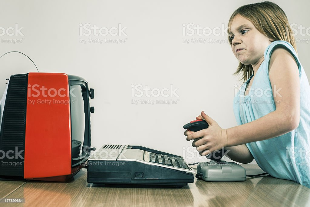 Little girl playing vintage video games with difficulty royalty-free stock photo
