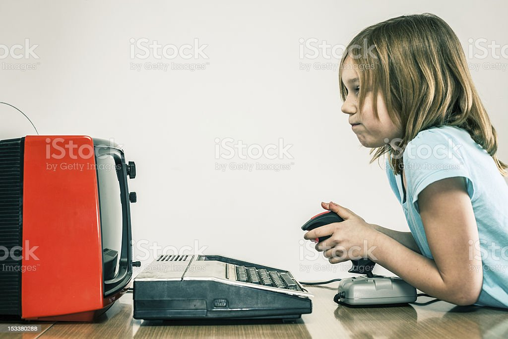 Little girl playing vintage video games with retro joy stick stock photo