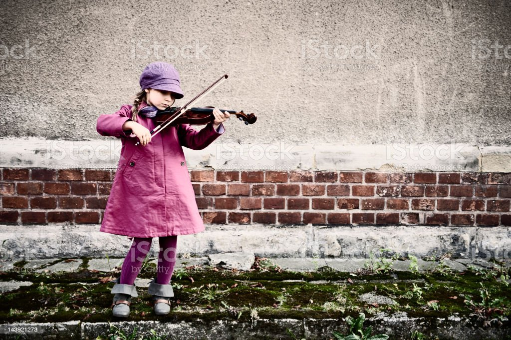 Little girl playing violin in front of an old building royalty-free stock photo