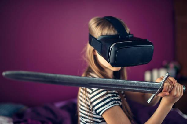 kleine mädchen spielen virtual-reality-spiel - lila waffe stock-fotos und bilder