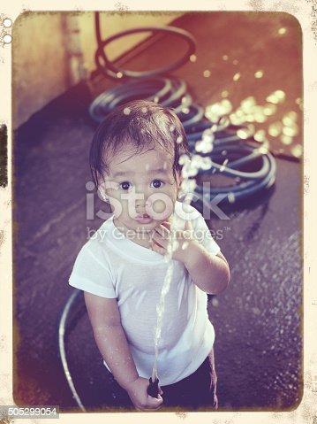 istock little girl playing water 505299054
