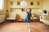 A cheerful cute young preschool girl is standing in the living room and enjoying playing with a white balloon and throwing it in the air.