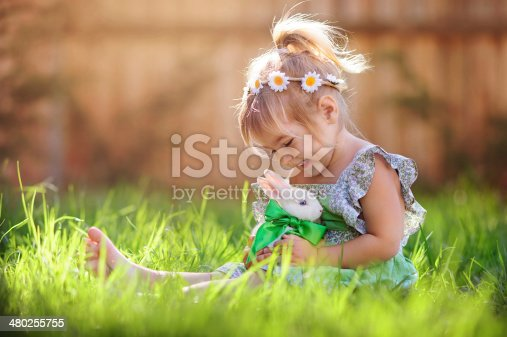 istock Little girl playing with a bunny on the grass 480255755