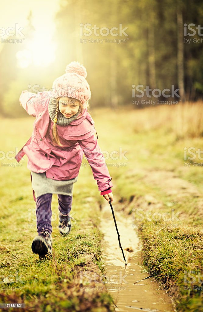 Little girl playing with a puddle stock photo