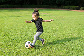 Little girl playing with a soccer ball